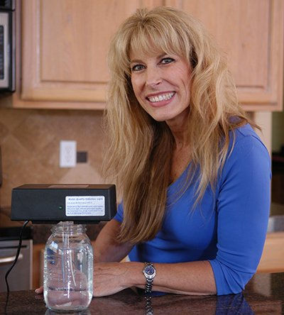 Woman in blue shirt smiling while using Micro Particle Colloidal Silver Generator - Basic Information Resources for New Owners of the Micro-Particle Colloidal Silver Generator