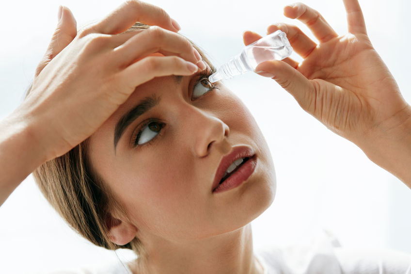 Woman using eyedropper with colloidal silver for eye infections