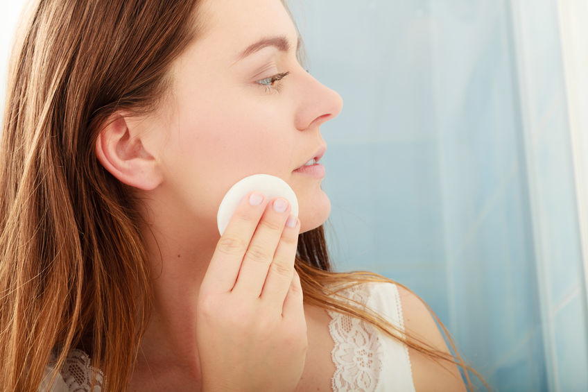 Woman wiping face with colloidal silver on cosmetic pad for acne treatment