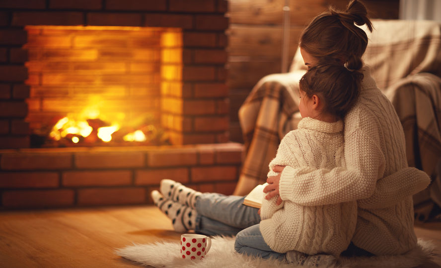 Mother and child daughter hugs and warm on winter evening by fireplace