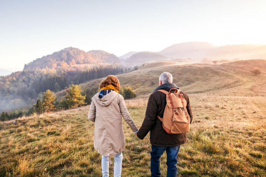 Healing Urinary Tract Infections with Colloidal Silver so You Can Enjoy Life. Active senior couple on a walk in a beautiful autumn nature, holding hands. Rear view.