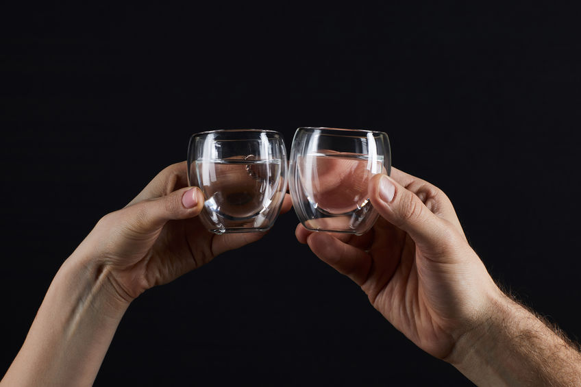 Man and woman clinking cheers with two small glasses of colloidal silver in water