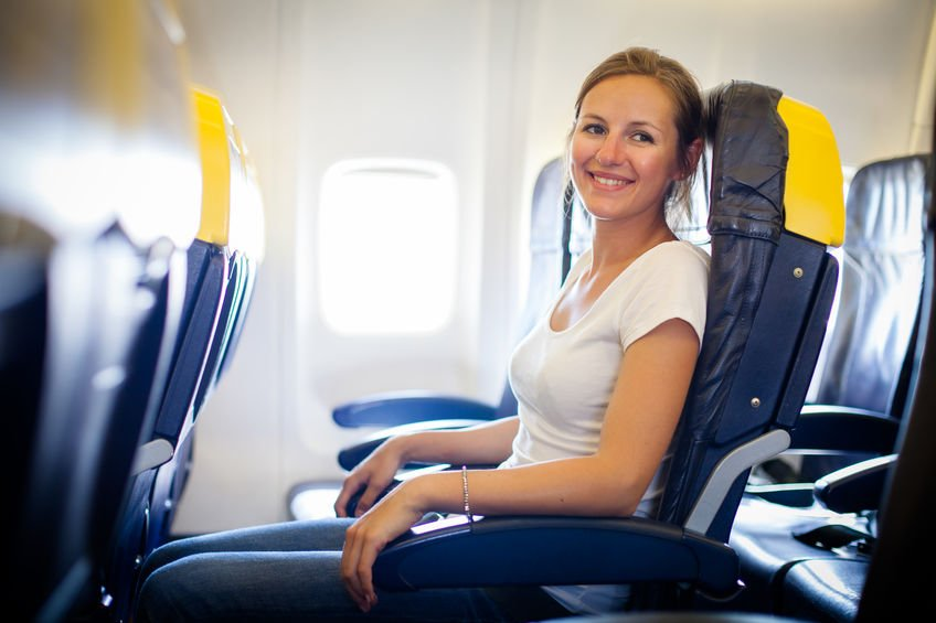 Pretty, young female passenger on board of an aircraft - Safer Airline Travel with Colloidal Silver?