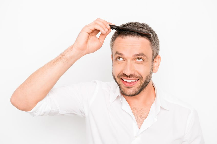Handsome man combing his hair with comb - How Colloidal Silver Can Help Heal Stubborn Dandruff