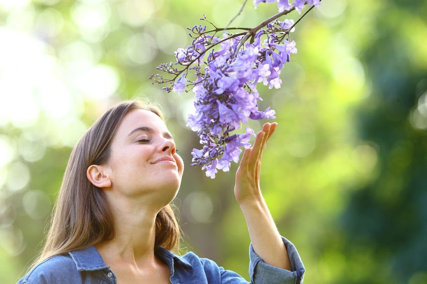 Candid woman smelling flowers in a park - Fight Sinus Allergies with Colloidal Silver!