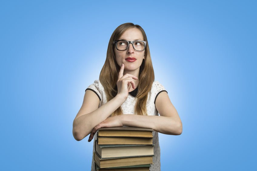 Young girl student with glasses leans on a pile of books and looks up with a pensive face on a blue background - Colloidal Silver Backed by Over 100 Year History of Research