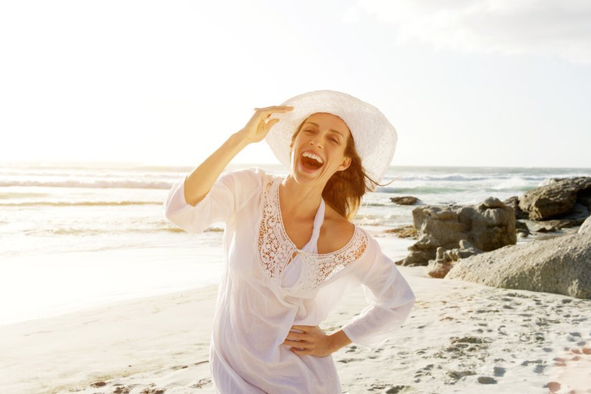 Carefree woman walking on beach with sun dress and hat - Healing Shingles Outbreaks with Colloidal Silver: Testimonials