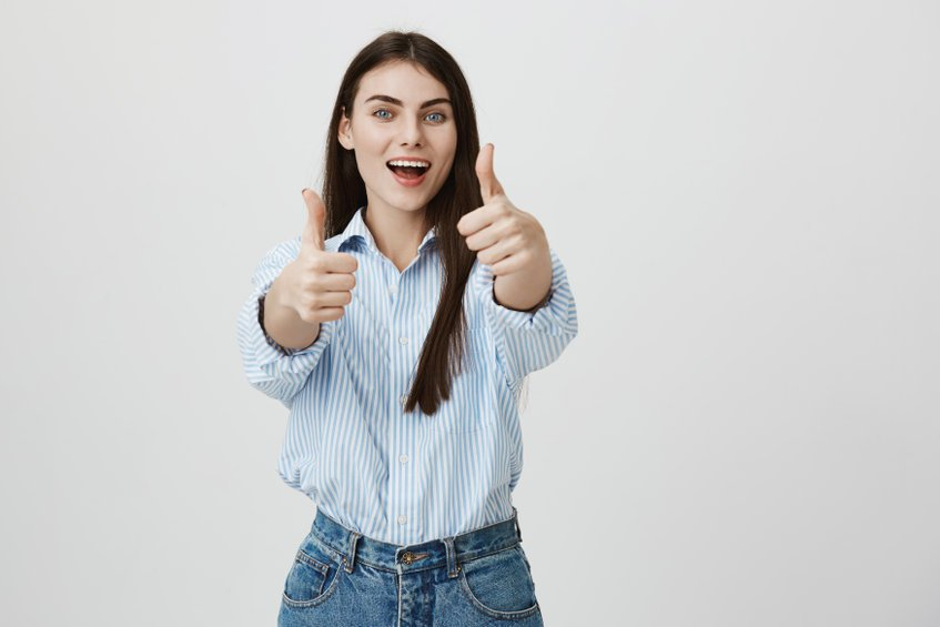 Portrait of successful young businesswoman, stretching hands with thumbs up, expressing satisfaction and approvement, standing over gray background. Woman shows her joy and positive answer - Make Sure You're Using the Right Water for Your Colloidal Silver!