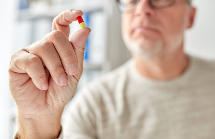 close up of man hand with pill - Can Silver Really Boost Efficacy of Antibiotics by Up to 1000 Times?